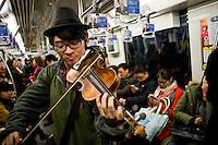 Un musicista suona il suo violino nella metropolitana di Shanghai.<br /> A musician playing violin in the subway car