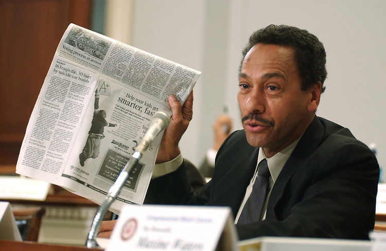 "10/07/04.ELECTION PREPAREDNESS--Melvin Watt, D-N.C., holds a copy of today's Charlotte Observer during a Congressional Black Caucus hearing called, ""The Long Shadow of the 2000 Election: Is America Ready to Vote on November 2nd?"" On the page is an Associated Press photo of a donkey transporting ballot boxes in the mountains northeast of Kabul, Afghanistan, where donkeys are the only means of distributing electoral kits in certain virtually inaccessible areas; Watt's point was that while the U.S. resorts to such extreme measures to make sure the right to vote is extended to every Afghan, it does not do enough within its own borders, even to the point of disenfranchising some..CONGRESSIONAL QUARTERLY PHOTO BY SCOTT J. FERRELL"
