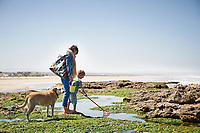 A woman watches whilst a boy casts his fishing net into a rock pool.