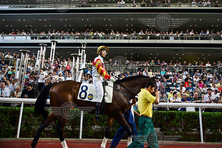A jockey with his horse in the parade ring before a race at the Hong Kong Jockey Club.