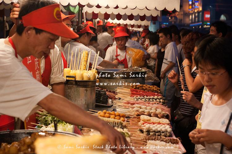 People buying food from vendors at the Wangfujing night markets, Beijing, China.