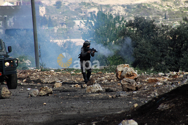 An Israeli security officer fires tear gas towards Palestinian protesters as clashes broke out during a demonstration against the expropriation of Palestinian land by Israel in the village of Kfar Qaddum, near the occupied West Bank city of Nablus, on March 14, 2014. Photo by Nedal Eshtayah