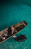 ZANZIBAR, Nungwi Beach, a Young Boy is releasing black ink to the water after Fishing Squids