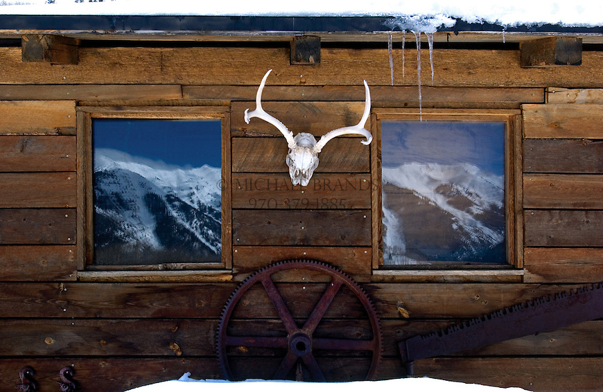 Highland ridge is reflected in the windows of a cabin on the backside of Aspen Mountain. Aspen, Colorado. Michael Brands photo.