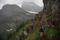 Hikers descend from Grinnell Glacier (rear, center) as a storm rolls in to the Many Glacier area of Glacier National Park in Montana.