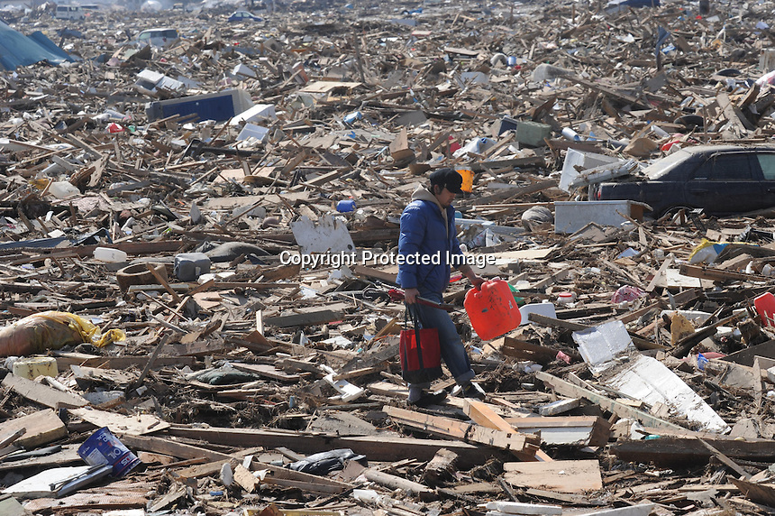 A man carries a can of fuel amongst the splintered remains of houses in the  town of Natori, after the Tsunami devastated the entire pacifc coastline of Japan after the earthquake and tsunami devastated the area Sendai, Japan.<br /><br />photo by Richard Jones/ sinopix