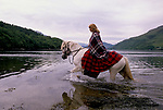 'CLAN, THE' SCOTLAND, GROUP WHO SPEND THEIR WEEKENDS AT A CAMP IN GLEN CROE, RECREATING THE LIFE OF A SCOTTISH CLAN BEFORE DEFEAT OF BONNIE PRINCE CHARLIE AT THE BATTLE OF CULLODEN IN 1746. HONORARY MEMBER DIANE DAVIDSON FORDING A RIVER WHILE LEADING THE CLAN ON A NINE MILE HORSE RIDE. SHE & HER FATHER OWN 2000 ACRES OF GLEN CROE & THREE HILLS & LIVE IN A COTTAGE WITH NO ELECTRICITY. SHE SEES THE CLAN AS A 'PERFECT ANTIDOTE TO THE GREY LIFE', 1989