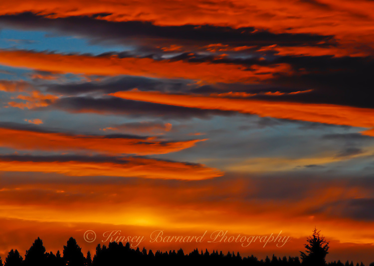Extraordinarily colorful sunset over the Kootenai Forest in Montana. The sun reflecting off clouds with just a hint of blue sky peeking through. The forest barely visible