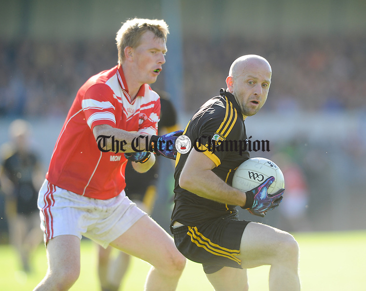 Pa Geaney of Naomh Eoin in action against David Neenan of Coolmeen during their junior football final at Cusack park. Photograph by John Kelly.
