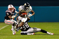 29 November 2008:  FIU running back Darriet Perry (28) attempts to break away from Florida Atlantic defensive back Ed Alexander (38) and defensive back Greg Joseph (3) in the FAU 57-50 overtime victory over FIU in the annual Shula Bowl at Dolphin Stadium in Miami, Florida.