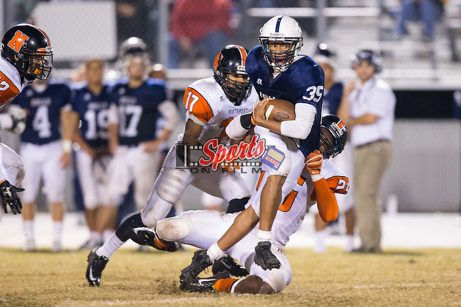 Remington Peters (35) of the Hickory Ridge Ragin' Bulls is tackled by Anthony Caldwell (25) of the Northwest Cabarrus Trojans late in the second half of play at Hickory Ridge High School on October 17, 2014 in Harrisburg, North Carolina.  The Ragin' Bulls defeated the Trojans 34-6.  (Brian Westerholt/Sports On Film)
