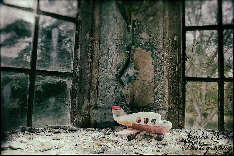 Child's toy plane by a window at derelict West Park Asylum, Epsom, Surrey, processed to emulate wet plate technique.