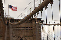 The American Flag waves in a strong wind on top of one of the towers of the Brooklyn Bridge, with patchy clouds behind it.  The tower's central pair of cables and lines angle up to the flag, bringing it to the focus.