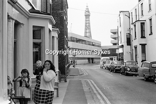 Young family outside their back street Bed anbd Breakfast hotel.  Blackpool Tower.  Lancashire, England. 1974