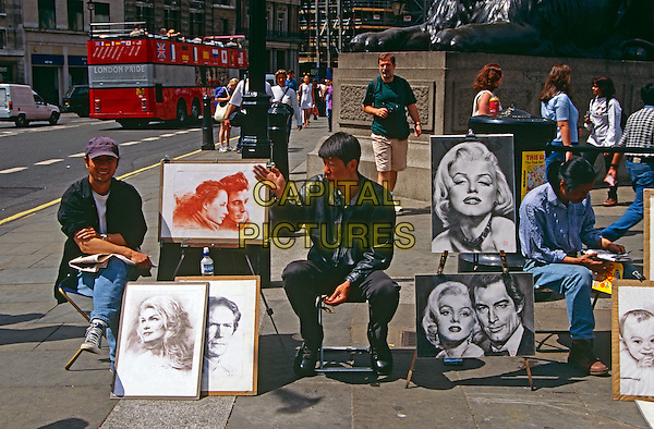 Street artists sitting beside pictures, Trafalgar Square, Westminster, London, England