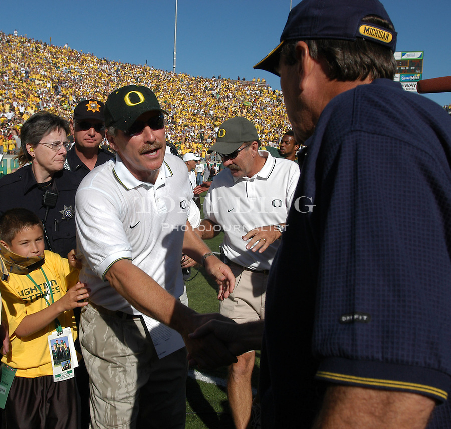 Oregon head coach Mike Bellotti shakes hands with Michigan head coach Lloyd Carr after the Oregon Duck's 31-27 upset of the Michigan Wolverines in Eugene, OR, on Saturday, September 20, 2003. (TONY DING/Daily)