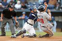 Asheville Tourists catcher Ryan Casteel #7 attempts to block the plate against a sliding Kyle Kubitza during a game against the Rome Braves at McCormick Field, Asheville, North Carolina April 19, 2012. The Tourists won the game 10-6  (Tony Farlow/Four Seam Images)..