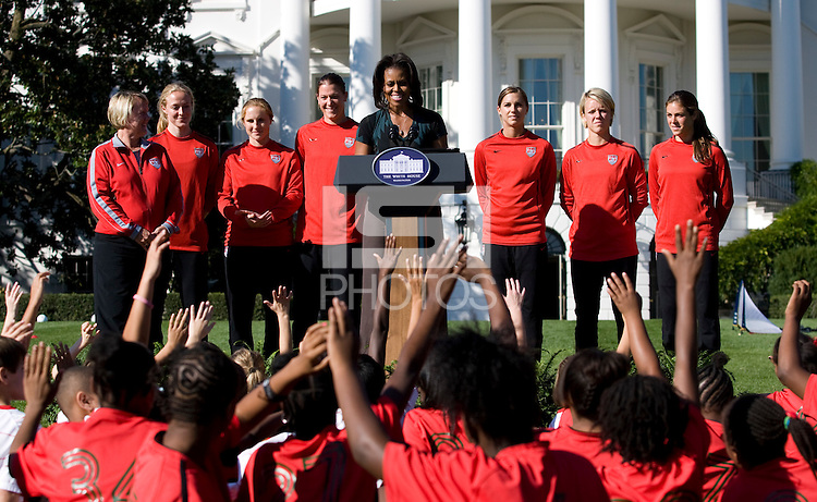 Michelle Obama speaks during a Lets Move! soccer clinic held on the South Lawn of the White House while flanked by members of the USWNT.  Let's Move! was started by Mrs. Obama as a way to promote a healthier lifestyle in children across the country.