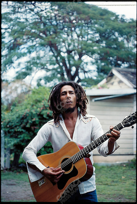 Bob Marley, with his guitar in the yard at home (Tuff Gong) in Kingston, Jamaica.  Originally photographed by David Burnett while on assignment for TIME magazine.  March 1976.