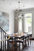 A contemporary chandelier  made of wire and glass resembling a delicate plant has been suspended above the dining table