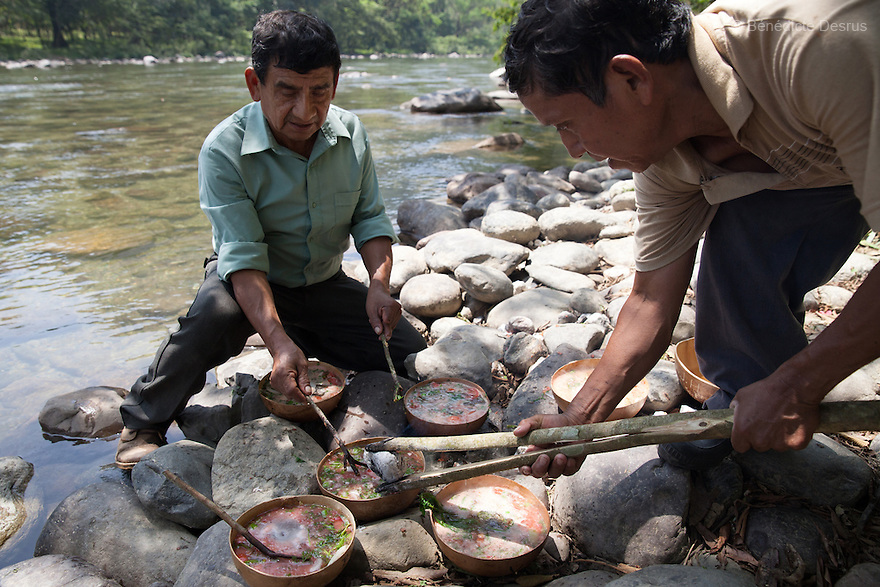 Don Victor Santiago Olivares (R) places a hot stone in the caldo de piedra on the banks of the Usila River in San Felipe Usila, Mexico on March 30, 2016. Caldo de piedra, or stone soup, is an ancestral dish of the indigenous Chinantec people of San Felipe Usila, a remote village in northern Oaxaca state, Mexico. Traditionally prepared by men in a ritual that dates back to pre-Hispanic times, the soup is cooked injícara(gourds) by glowing-hot white river rocks that have been heated on a bonfire of orangewood. Ingredients include whole mojarra fish, tomatoes, onion, garlic, chile, epazote, cilantro and fresh water; the soup is seasoned with lime and salt and eaten on the banks of the Usila river. Photo by Bénédicte Desrus