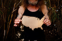 """Ventura, California, July 23, 2010 - A portrait of Tim 'Timbow' Bowman holding a cardboard map of the United States near his campsite along Ventura River bottom. Bowman has been homeless and living along the river since the early 1990's. In 1987 Bowman's 18-month-old daughter, Miranda Laurel, died from Lyme disease. His wife left him soon afterwards. A year later he fell through a plate glass window while working on a construction site, leaving him disabled and unable to work construction. He says the loss of his wife and daughter and his struggles with work sent him into a spiral. He eventually lost his home. He says he lives in the 300+ community along the river bottom because he """"feels at home."""" Adding, """"I feel loved down here. Up there is nothing but trouble."""" The two-mile stretch of river bottom from the Pacific to Stanley Road is home to about 300 homeless, who have carved tunnels and paths into the tall grass and bamboo. Bowman, who survives off of SSI, says, """"I lead an honest life. I don't steal, I don't rob and I share whatever I can."""" .."""