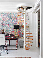 A spiral staircase leads up from the study area of the open-plan living space to the master bedroom on the floor above