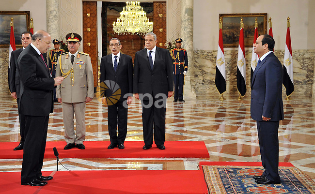 A handout picture released by Egyptian Presidency shows Egyptian President Abdel-Fattah el-Sissi, right, listens to the new ministers during a swearing-in ceremony for new cabinet ministers at the presidential palace in Cairo, June 17, 2014. El-Sissi chaired the first meeting of his new Cabinet on Tuesday, shortly after its members were sworn in at the presidential palace in Cairo. apaimages\Egyptian Presidency