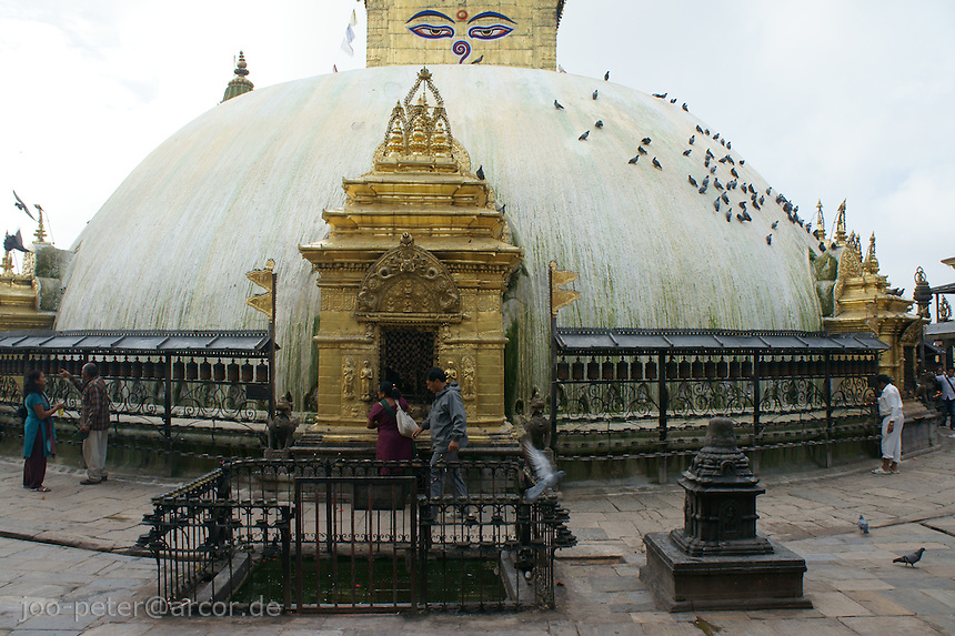 stupa of buddhist temple Swayambhu with devotees  in Kathmandu, Nepal, September 2011