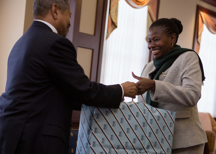 Ohio University President Roderick McDavis, left, and Mrs. Grace Muzila, right, of the Ministry of Education Skills and Development, Botswana, exchange gifts before a luncheon at Baker Center on January 21, 2014. The discussion and luncheon were hosted by the Ohio University Center for International Studies.