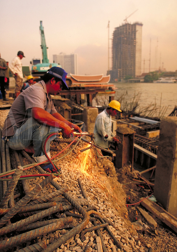 The Peninsula. The last of the mid 90's construction boom in Bangkok, Thailand. Close up of laborer using a cutting torch on rebar. Other high rises under construction in background. Bangkok, Thailand.