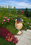 Vashon-Maury Island, WA<br /> Driscoll garden, with decorative urns and stone path framing a view of Quartermaster Harbor