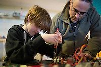 Owen Nannarone, of Scituate, Mass., is a 10-year-old inventor.  Seen here working in his family's basement with his father Len Nannarone, Owen likes to take apart and repair electronics and motors.  He recently developed a prototype for a golf tee that can measure the speed and direction of a golf ball as it's hit.  Two years ago, he developed something called the EZ-Cinch Net, a fishing net with closeable compartments that allow him to collect multiple turtles or frogs from nearby bogs without the animals contacting one another.