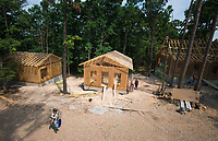 NWA Democrat-Gazette/CHARLIE KAIJO Volunteers construct homes, Friday, June 8, 2018 on Passion Play Road, across the street from the Washington Regional clinic in Eureka Springs. <br /><br />Eight tiny houses are being built in Eureka Springs, which has a dearth of affordable housing. They're being constructed by 66 volunteers from 13 states with World Mission Builders. They began work on Monday (June 4) and should finish most of the construction by the end of next week (June 15). Then local volunteers will finish out the interiors and put shingles on the roofs. The first eight houses are part of what will be called ECHO Village. Plans are to eventually have 26 houses in the village. It's a project of Eureka Christian Health Outreach, which bought 10 acres for the village. The same group started ECHO Clinic in Eureka Springs in 2005. It provides free medical care to the uninsured and people on a low income.
