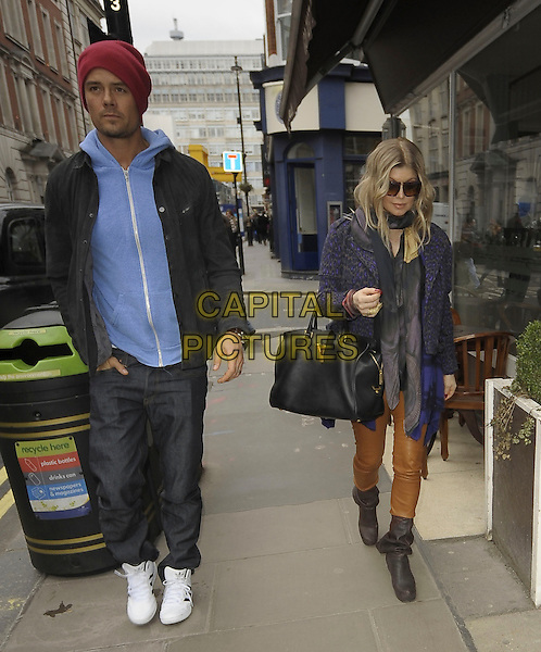 Josh Duhamel & Fergie (Stacy Ann Ferguson) .Spotted in central London, England..21st February 2013.married husband wife black eyed peas bep full length red beanie hat black jacket jeans denim white trainers sneakers purple brown leather trousers shoes boots sunglasses shades blue hooded top hoodie hoody scarf leopard print hand in pocket bag purse .CAP/IA.©Ian Allis/Capital Pictures.