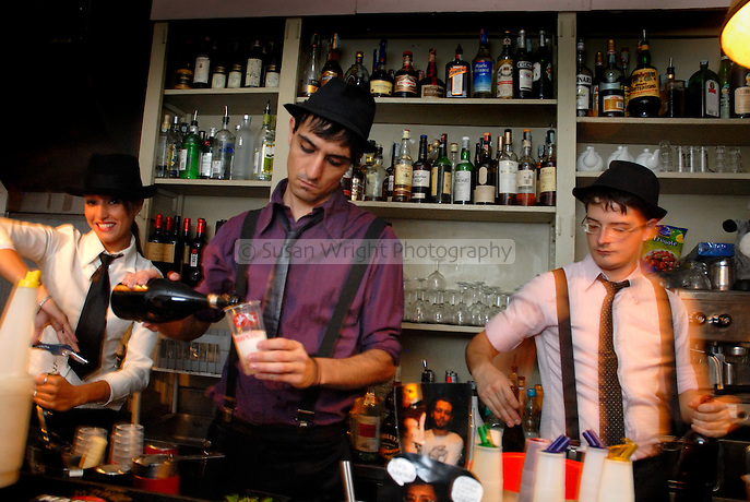 Bartenders serving drinks, at popular student bar in Rome, Italy