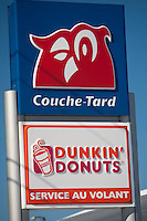 "A Couche-Tard and Dunkin' Donuts ""service au Volant"" (Drive-through) sign is seen on the Rue de l'Aeoroport Street in Quebec City February 24, 2009. Now owned by Alimentation Couche-Tard in the province of Quebec, Dunkin' Donuts is an international donut and coffee retailer."