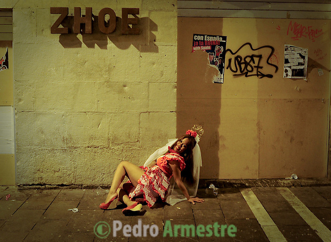A woman poses for the photographer smiling during the San Fermin Festival, on July 09, 2012, in Pamplona, northern Spain. The festival is a symbol of Spanish culture that attracts thousands of tourists to watch the bull runs despite heavy condemnation from animal rights groups . (c) Pedro ARMESTRE