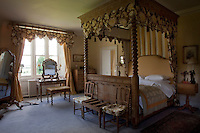 The elaborately turned four-poster bed and window curtains are both adorned with matching scalloped pelmets
