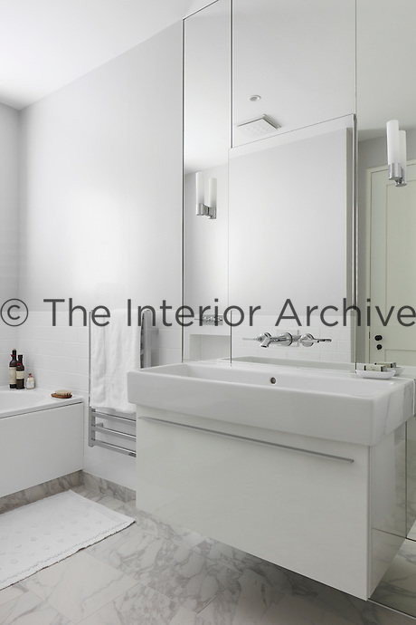 A pale grey and white bathroom with marble floor tiles and a long wash basin backed with a mirror, in which the tap has been mounted
