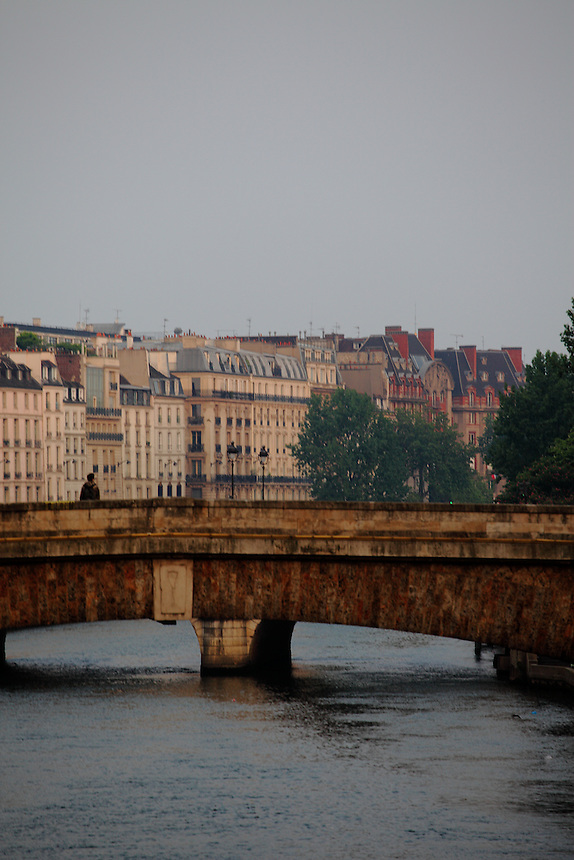 A bridge onto the Seine river in Paris with a person, in the sunrise light. There are some trees and the typical buildings of the Rive Gauche on the background. Digitally Improved Photo.