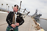 A bagpiper sends off the final voyage of the battleship USS Iowa from Berth 51 to its new home at Berth 87 in San Pedro, Los Angeles, CA where it opens as a museum ship in July 2012.