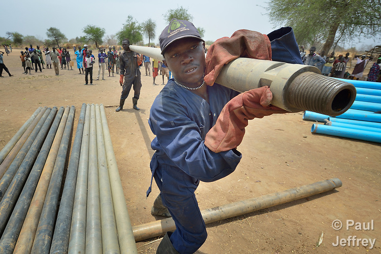 Workers carry pipe as they drill a well on April 7, 2017, in Rumading, a village in South Sudan's Lol State where more than 5,000 people, displaced by drought and conflict, remain in limbo. In early 2017, they set out walking for Sudan, seeking better conditions, but were stopped from crossing the border. They remain camped out under the trees at Rumading, eating wild leaves as the rainy season approaches. <br /> <br /> In early April, Norwegian Church Aid, a member of the ACT Alliance, began drilling the well in the informal settlement and distributed sorghum, beans and cooking oil to the most vulnerable families. <br /> <br /> The ACT Alliance is carrying out the emergency assistance in coordination with government officials and the local Catholic parish.
