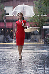 Young woman in a red elegant dress with an umbrella walking on a rainy day on a city street