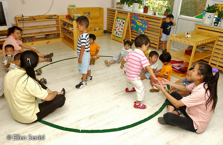 Beijing, China .Little Oak Children's House: private day care center and private elementary school..Students do song and movement activity with teacher and aides while sitting in circle on floor..© Ellen B. Senisi