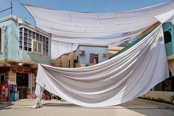 Shooting the series &ldquo;Al Halal&rdquo;, Egypt Mars 2017 (Cedar Group). Very popular in Egypt, the style of series &ldquo;shaabi&rdquo; (from the people) takes place in poor areas. In a society where social classes are sharply divided, television has to be for everyone. On this shoot, the studio replicates a quarter of Cairo. This sheet is mounted to be used to filters the sunlight.<br /> <br /> Tournage de la s&eacute;rie &quot;Al Halal&quot;, Egypte Mars 2017 (Cedar Group). Les Egyptiens sont friands des s&eacute;ries de style &quot;shaabi&quot; (populaires), dont les histoires se d&eacute;roulent dans des quartiers pauvres. Dans une soci&eacute;t&eacute; o&ugrave; les diff&eacute;rentes classes sociales sont imperm&eacute;ables les unes aux autres, la t&eacute;l&eacute;vision doit plaire &agrave; tous. Sur ce tournage, le studio r&eacute;plique un quartier du Caire. Le voile qui permet de filtrer la lumi&egrave;re du soleil est en train d'&ecirc;tre mont&eacute;.