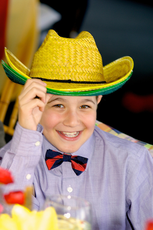 Boy wearing colorful straw cowboy hats at a rodeo themed Mitzvah.