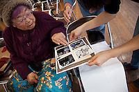 Tsunami refugee, Tokiyo Sato (88) chooses photos to put in her new album during the Photohoku event in Iwaki, Fukushima, Japan. Sunday January 26th 2014