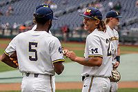 Michigan Wolverines outfielder Jordan Brewer (22) laughs with teammate Christian Bullock (5) before Game 11 of the NCAA College World Series against the Texas Tech Red Raiders on June 21, 2019 at TD Ameritrade Park in Omaha, Nebraska. Michigan defeated Texas Tech 15-3 and is headed to the CWS Finals. (Andrew Woolley/Four Seam Images)