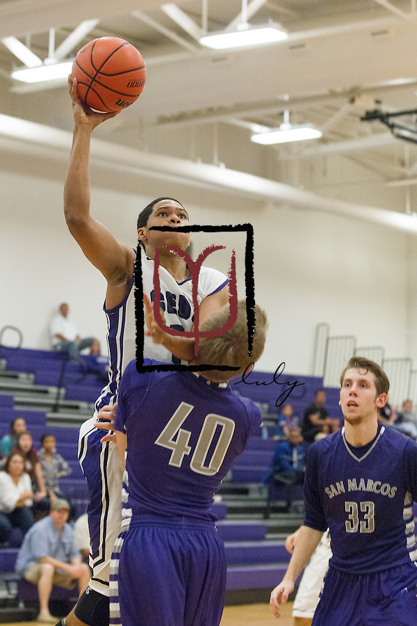 Cedar Ridge's Nolan Ferree attempts to shoot over San Marcos' Truett Newton Friday at Cedar Ridge Gym.  The Raiders won the game in overtime 88-87.  (LOURDES M SHOAF for Round Rock Leader.)